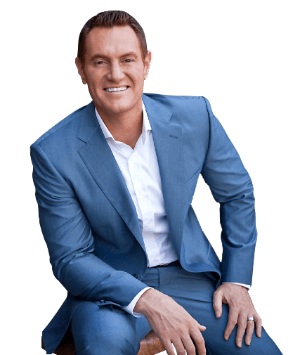 Darren Hardy wearing a blue suit sitting down on a chair in a studio setting giving testimonial to June Spring Multimedia