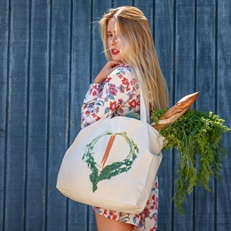 A blonde woman carrying a white tote shopping bag with bread and vegetables in it