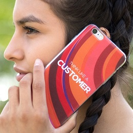 """A woman holding a phone with a """"Think Like A Customer"""" printed jelly case beside her ear"""