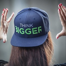Woman wearing a think bigger printed blue cap and both hands on the side of her head