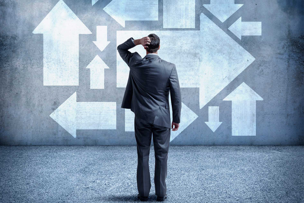 Confused businessman standing in front of the wall with arrows at different directions