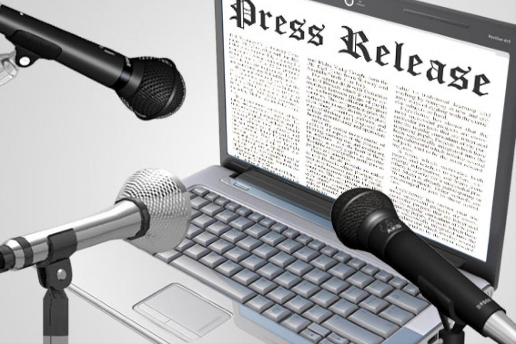 Laptop showing press release article with three microphones pointing to it