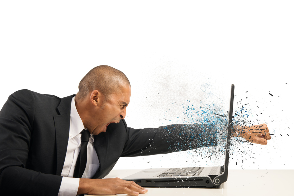 Stressed and frustrated businessman punch his laptop