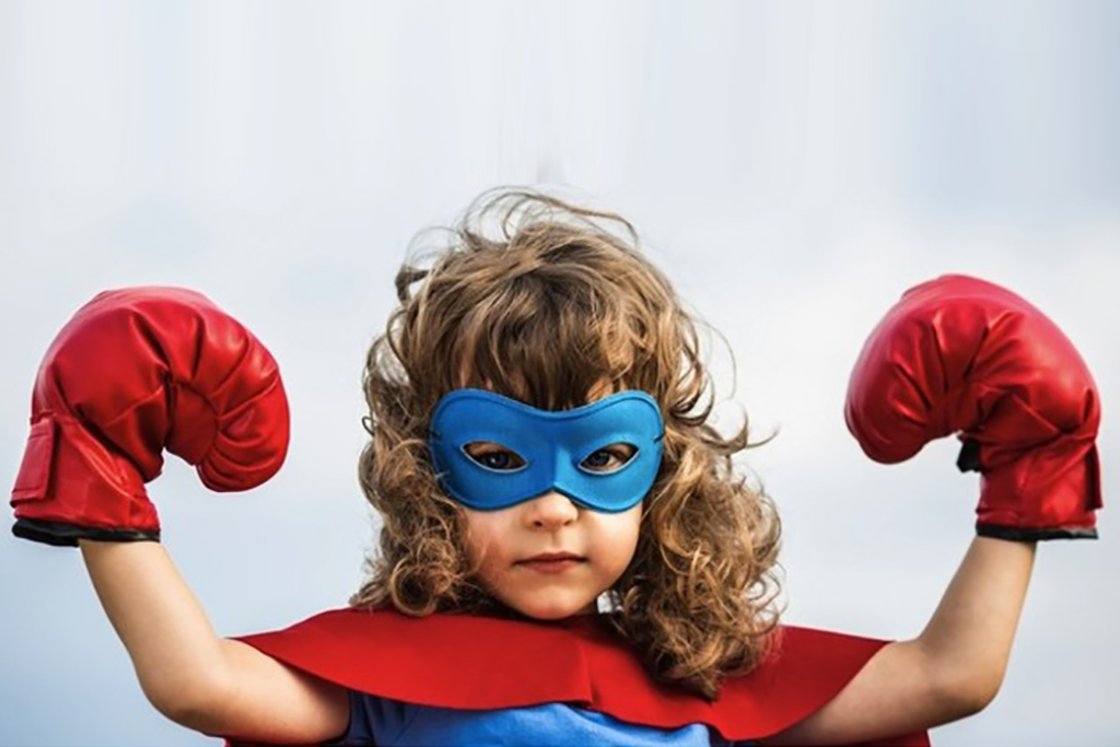 Superhero girl kid wearing boxing gloves against blue sky background
