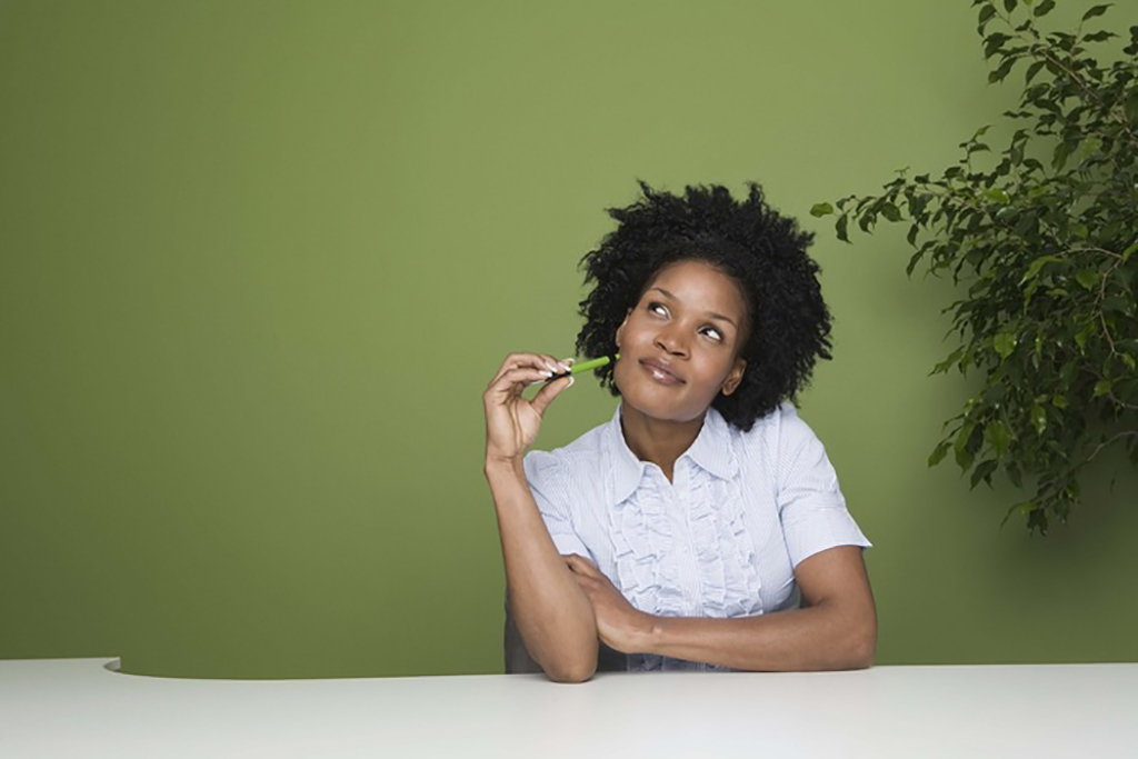 An african girl is sitting while thinking and holding green pen near the tree on green background