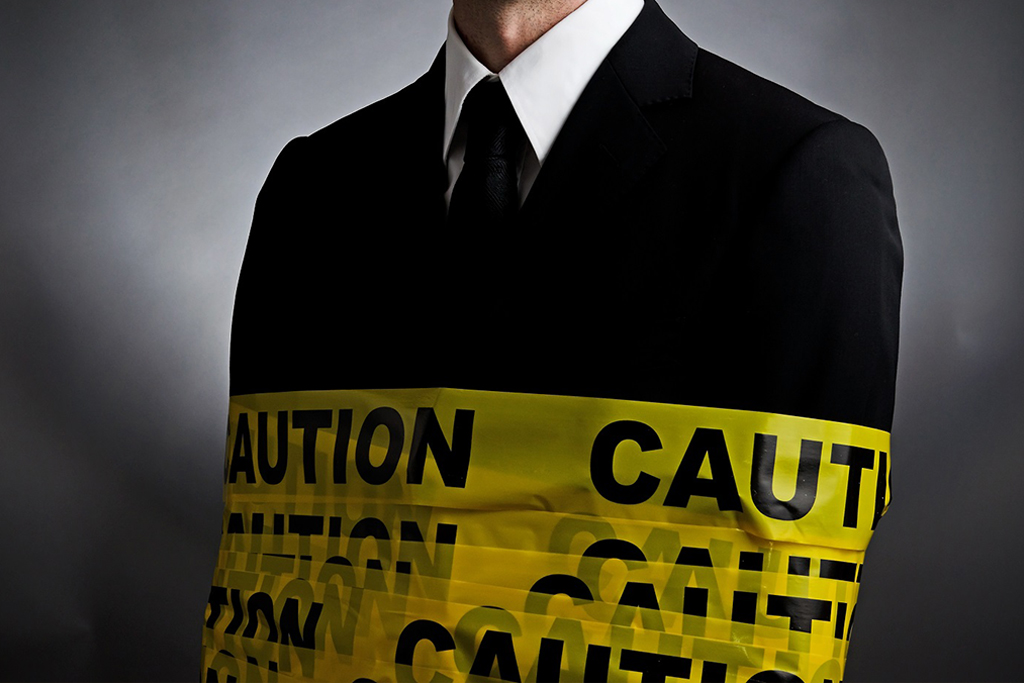 Businessman is wrap with a caution tape