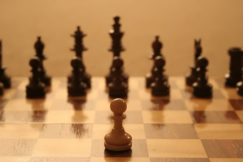 A light pawn at a chess board stands out from the dark pieces