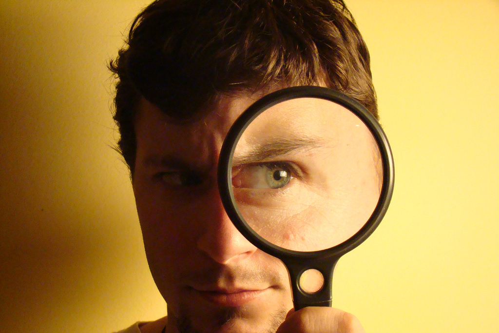 Young man using magnifying glass