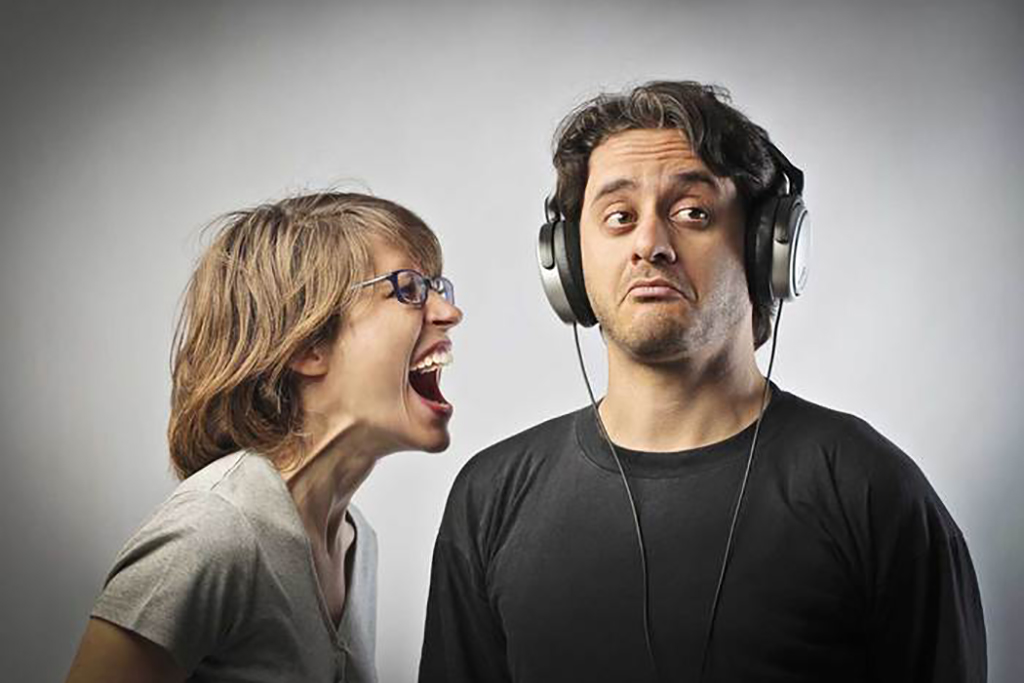 Angry wife screaming against her husband but not listening to her because his wearing headphones