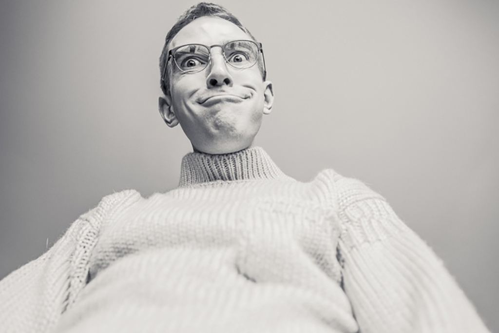 Man wearing glasses in knitted shirt making funny face
