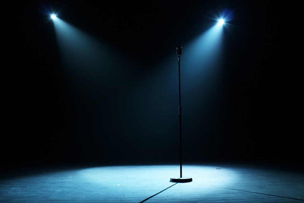 A microphone stand on the center of a stage lit by two spotlights