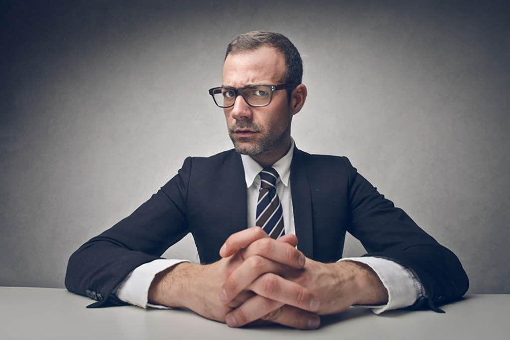 Serious businessman sitting with hands resting on the desk