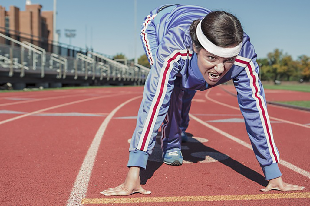 Young excited athlete runner in a position of readiness to start running in a sports stadium