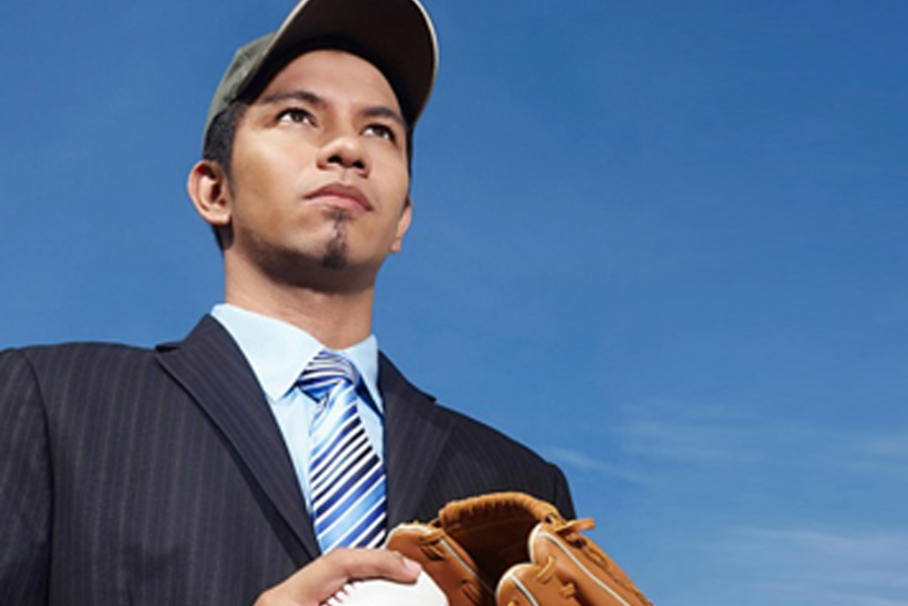 Businessman in black suit wearing a cap and holding a baseball and gloves
