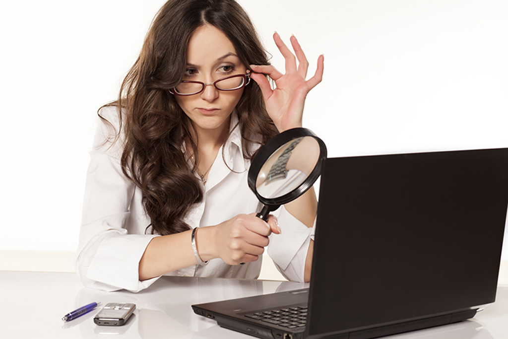 A female wearing eyeglasses in corporate attire sitting next to her laptop holding a magnifying glass