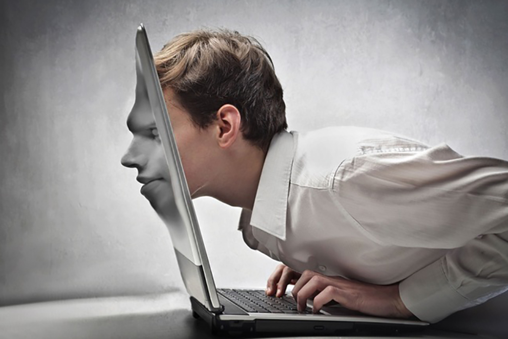 Young businessman passing his face through a laptop screen