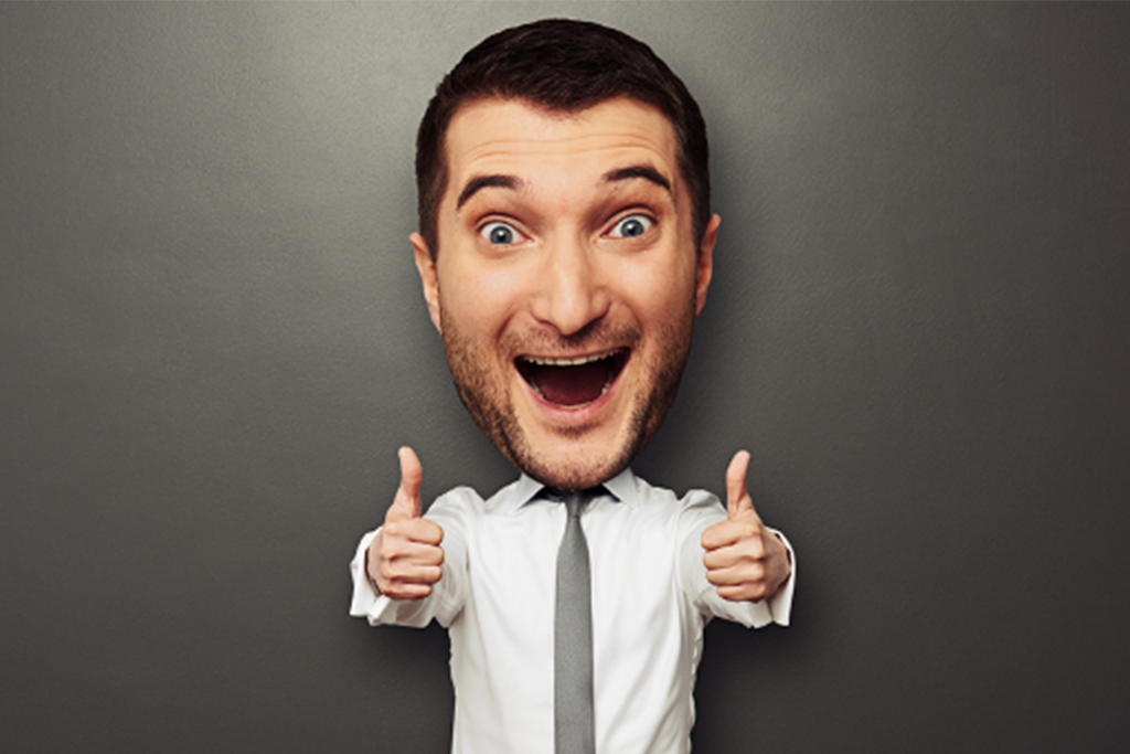 Young happy businessman with big head showing ok sign