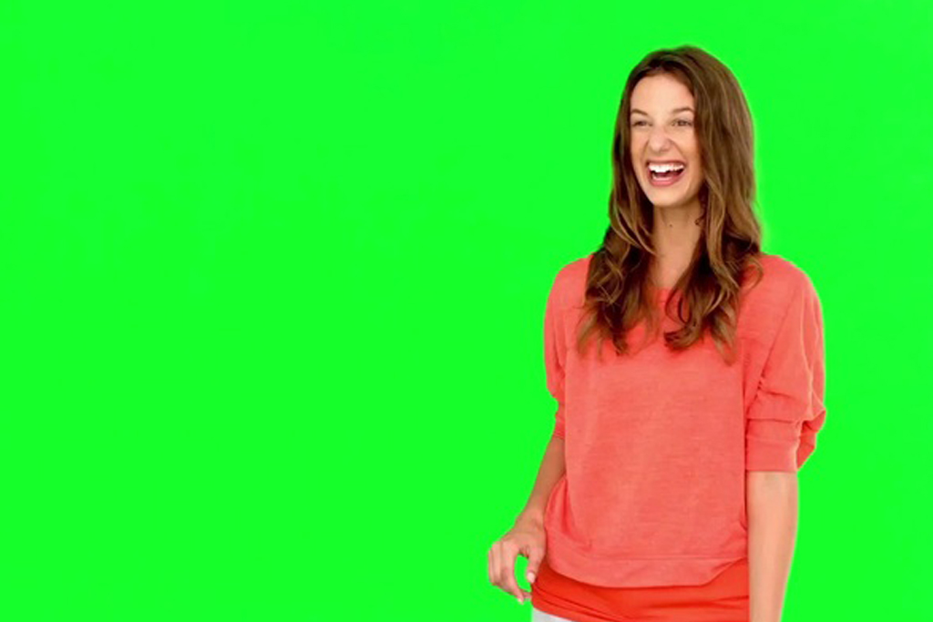 Woman wearing pink blouse smiling happily on green background