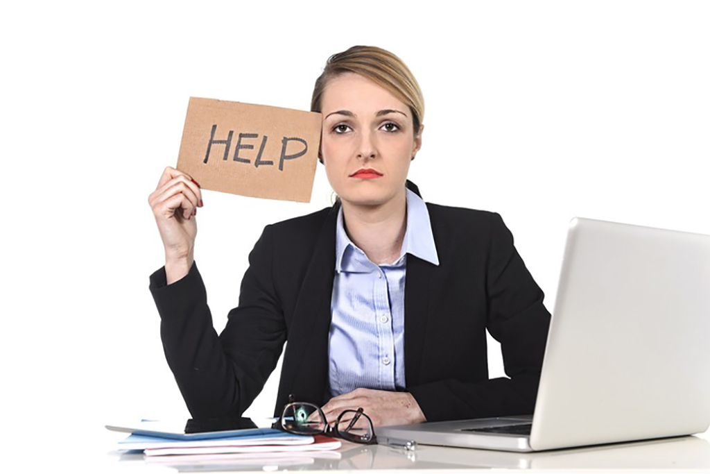 Young attractive frustrated and tired businesswoman holding help sign message
