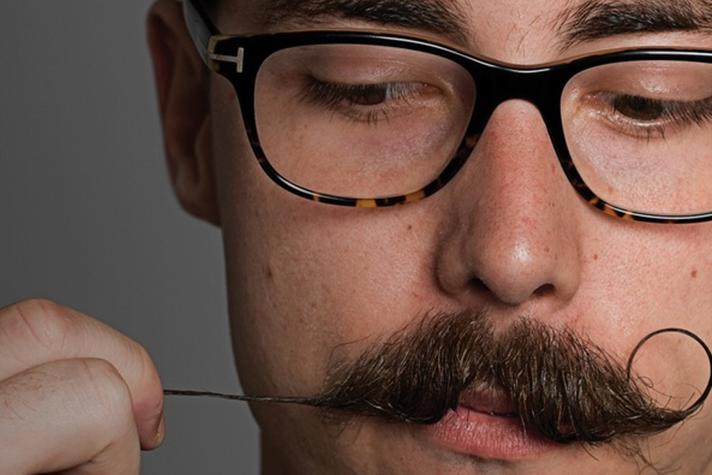 Man wearing glasses holding his mustache