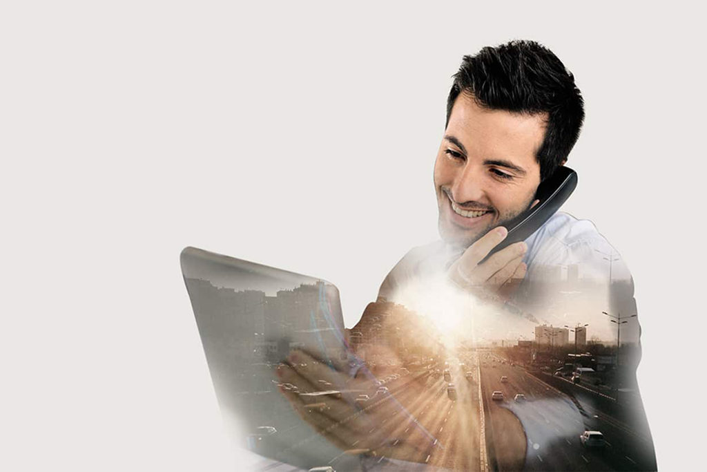 Handsome man using phone while holding tablet and smiling