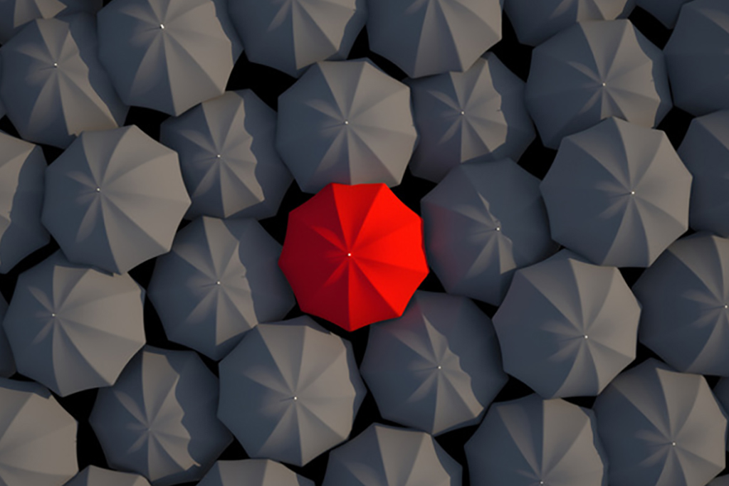 Standing out from the crowd with a red umbrella against a group of gray umbrellas