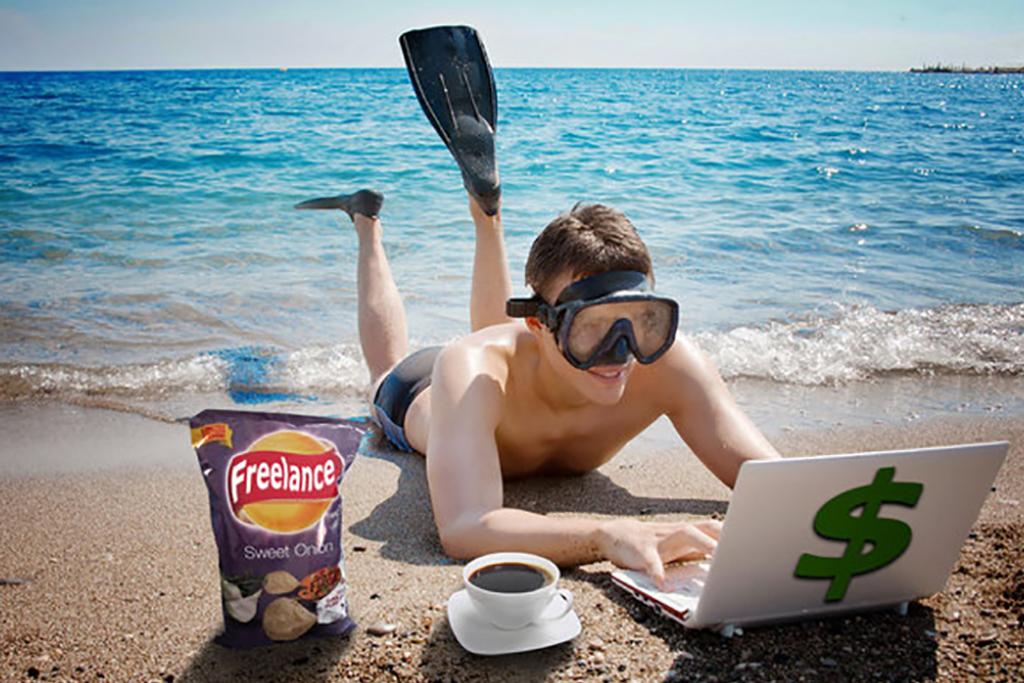Smiling man with googles and flippers lying on sand looking at laptop with chips and coffee beside it