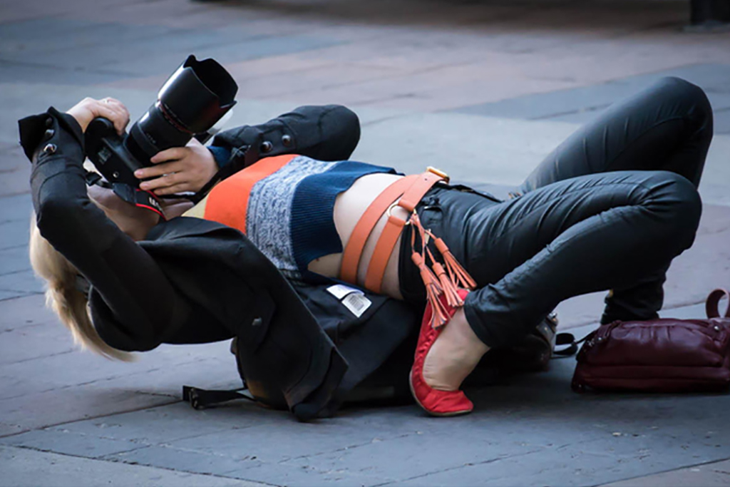 Photographer lying against her bag on the ground taking picture