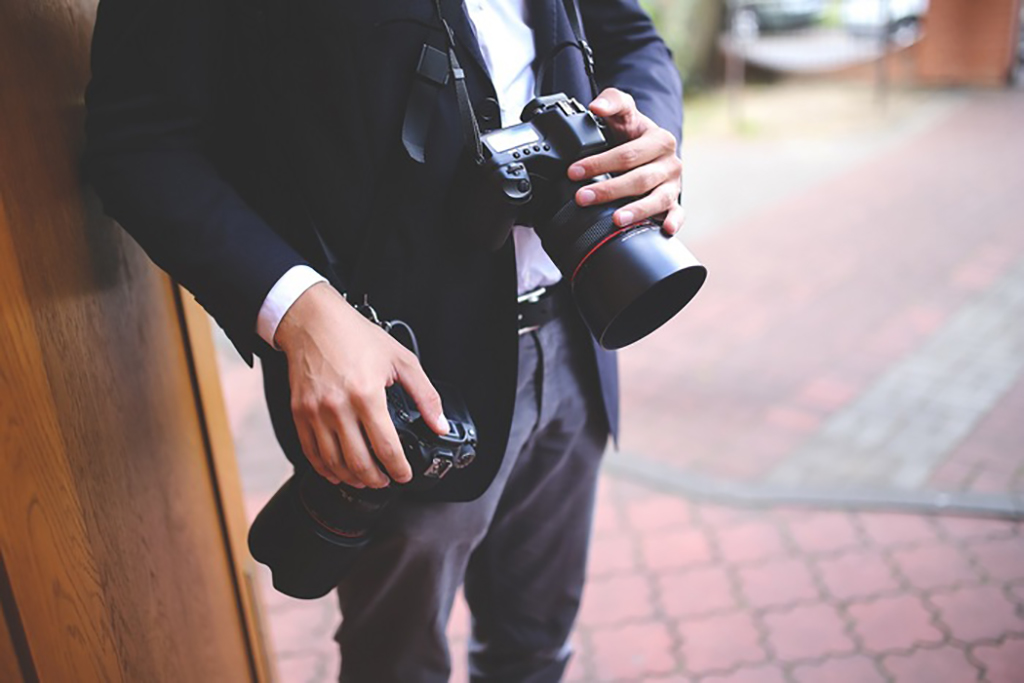 Man in black suit holding two camera