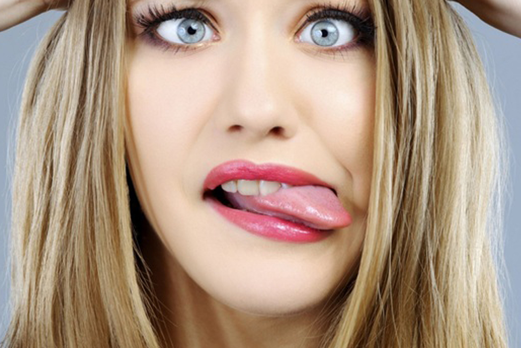 Portrait of happy blonde young woman sticking her tongue out