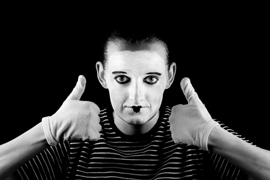 A man painted face in black striped shirt giving thumbs up