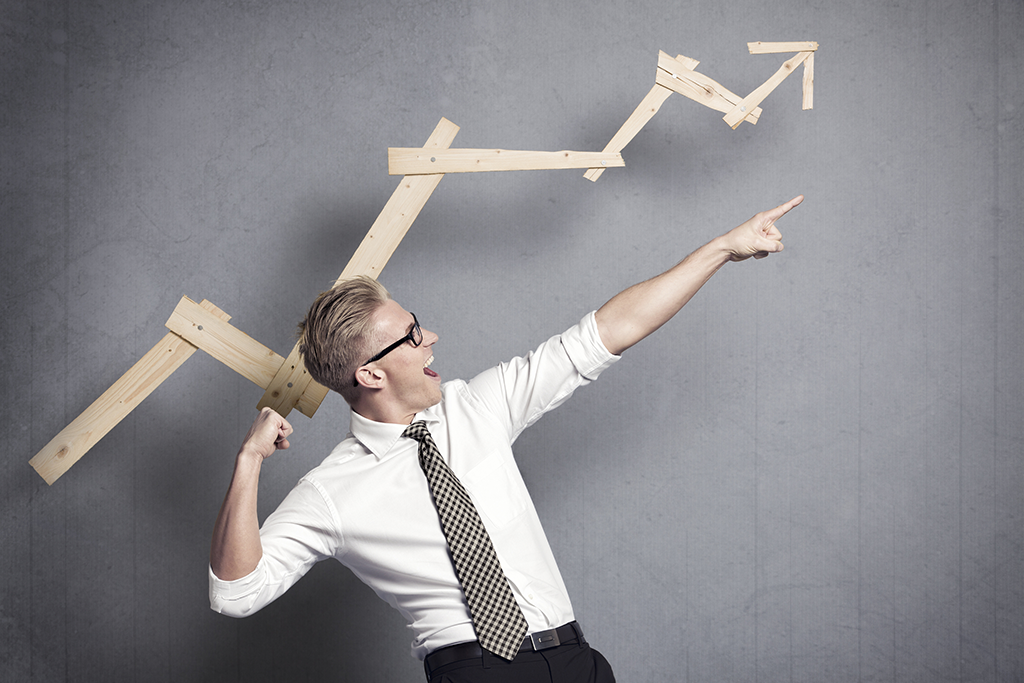 Happy talented businessman pointing arm upwards in front of ascending business graph on grey background