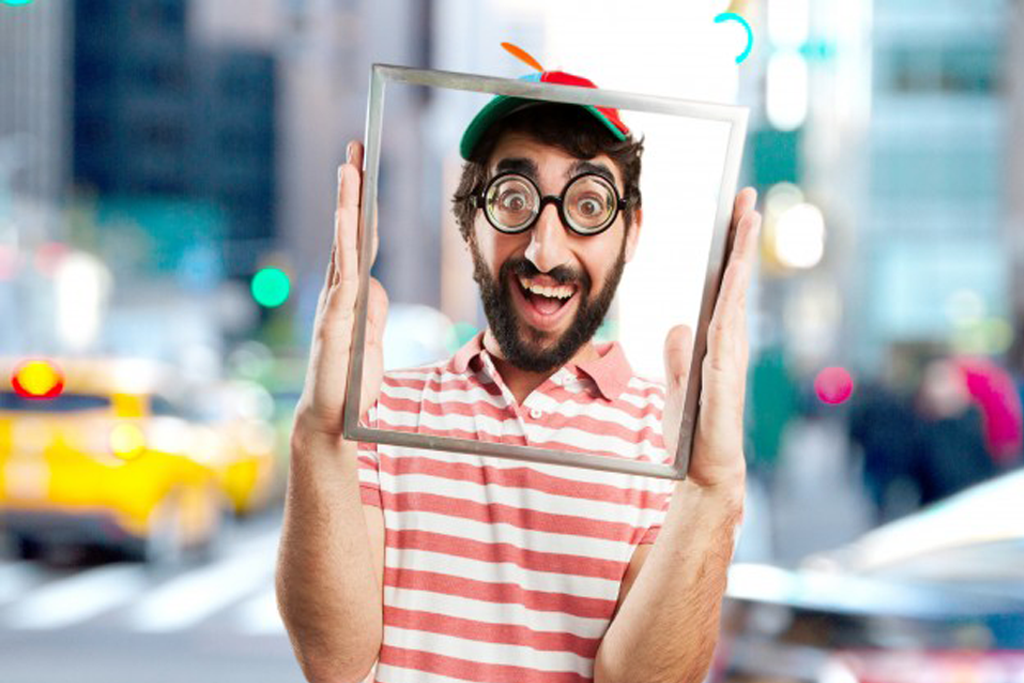 Playful portrait man in a red stripe shirt holding picture frame in front of his face on unfocused background