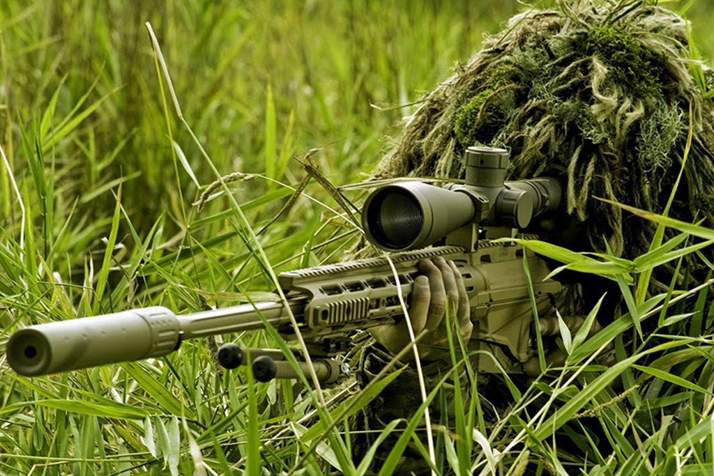 Soldier holding ripple camouflage on grass