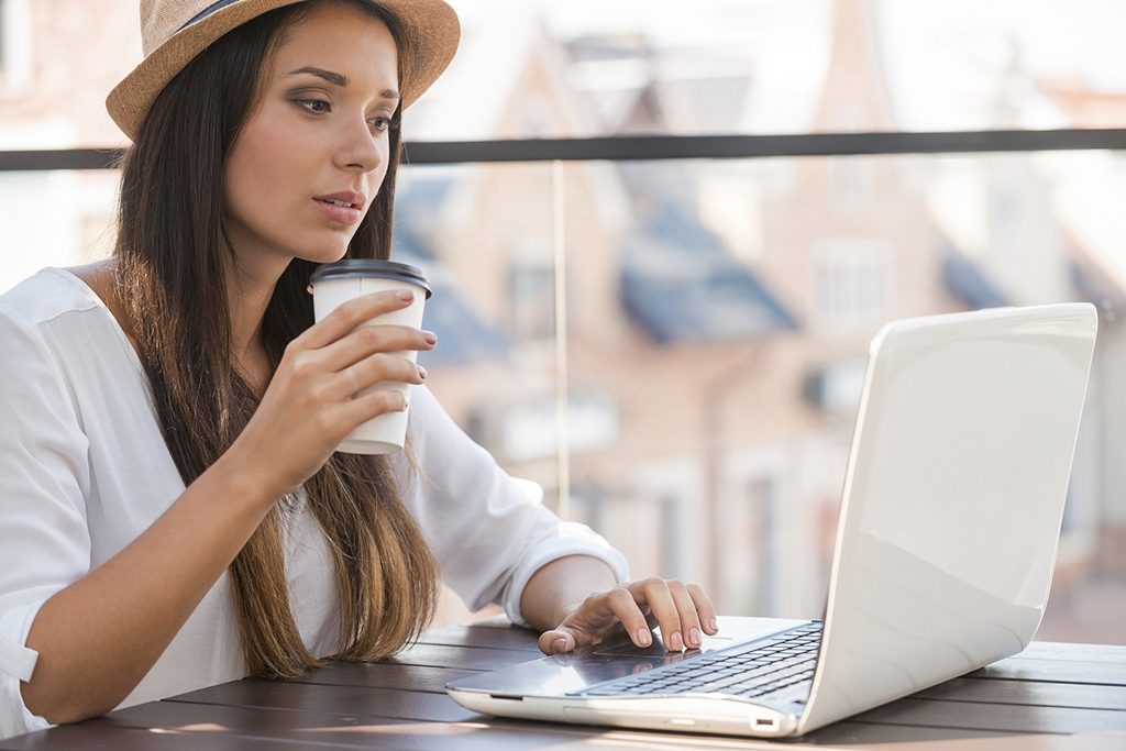 Beautiful young woman in funky hat working on laptop while sitting outdoors