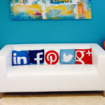 Social media icons printed on the pillow lined up in the sofa