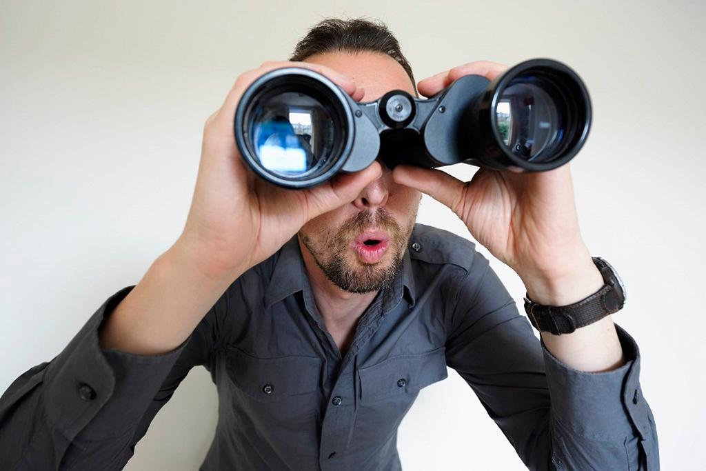Businessman wearing dark blue sleeves seeking with binocular