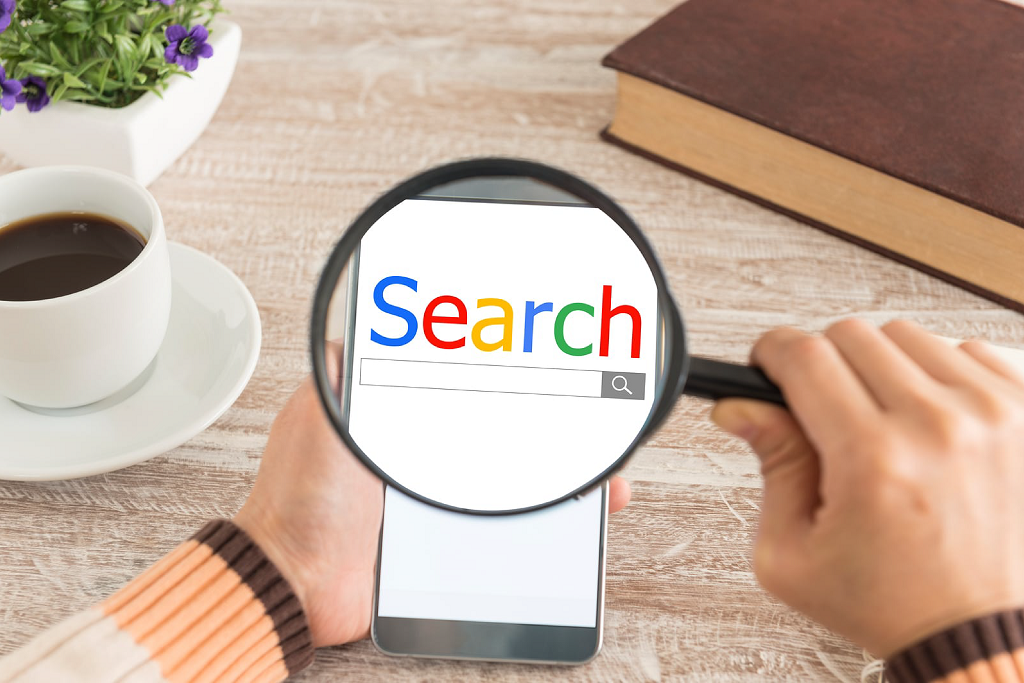 A hand holding a mobile phone on the left and right hand holding a magnifying glass focusing on google search