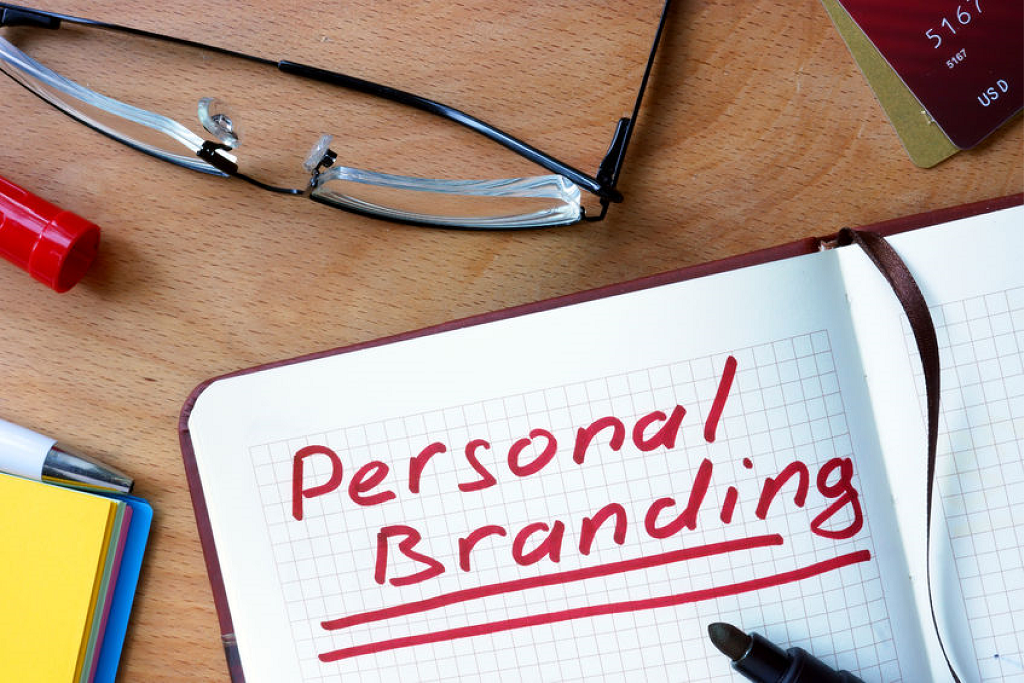 A notebook with tagline 'Personal Branding' on the wooden table with eyeglasses at the side
