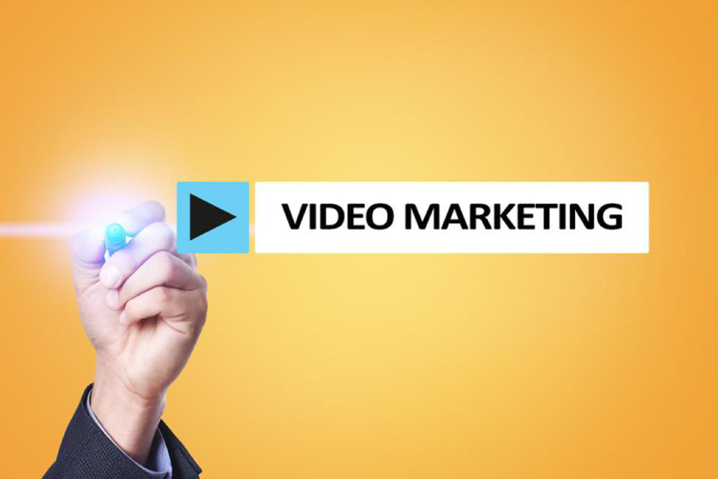 A hand holding a lighted pen focusing on a search bar with a play button and tagline 'Video Marketing'