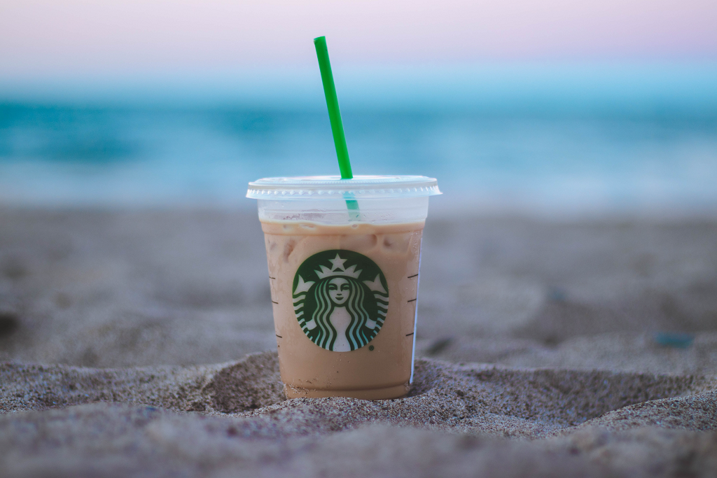 A cup of coffee iced drink from popular starbucks brand buried bottom on the sand by the beach