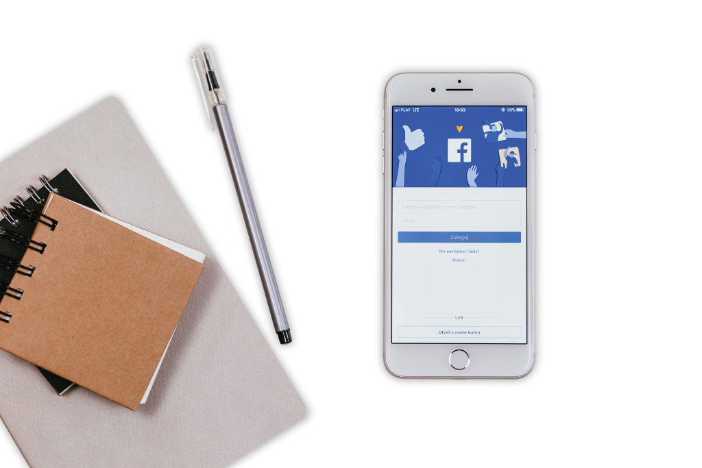 A smartphone with facebook log in on the screen and a notebook with a pen beside it