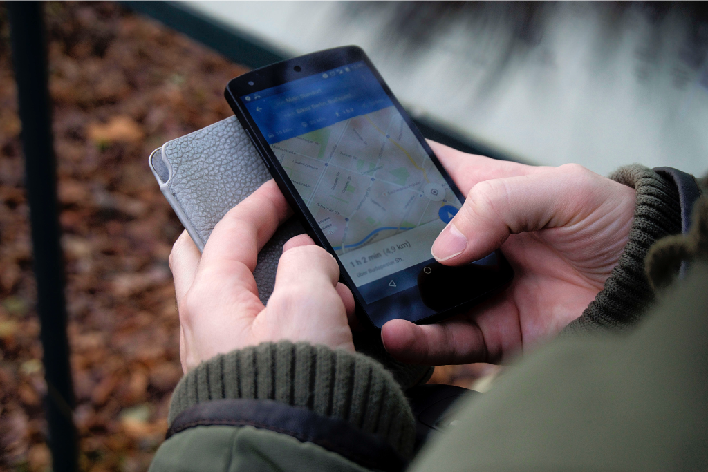 A hand holding a mobile phone while tracking a map for location