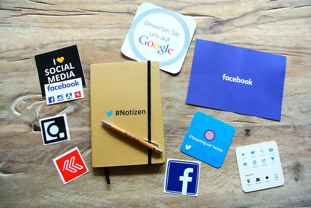 A notebook on the table with social media icons surrounding it