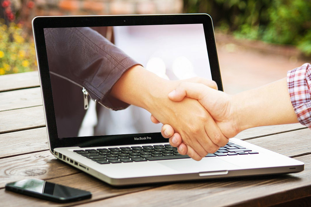 A hand coming out from a Laptop computer shaking hands with a guy's arm in checkered sleeves
